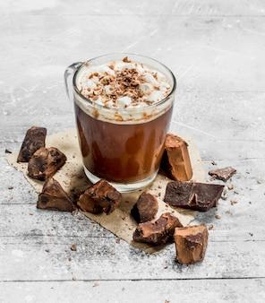 Горячий шоколад с кусочками горького шоколада и зефира на деревенском столе.
