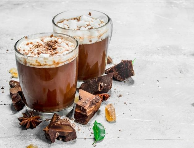 Горячий шоколад с кусочками горького шоколада и зефира на деревянном столе.