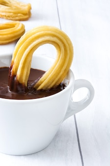 Hot chocolate with churros on white wood. spanish breakfast