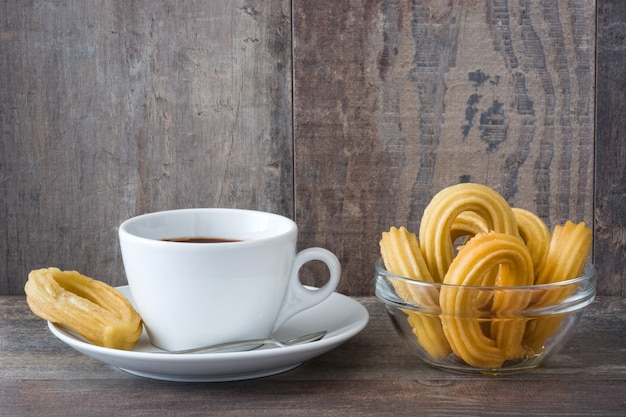Hot chocolate with churros on wooden table spanish breakfast