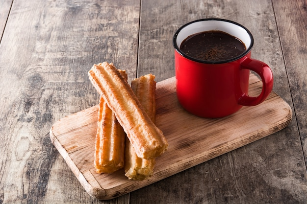Hot chocolate with churros on wooden table