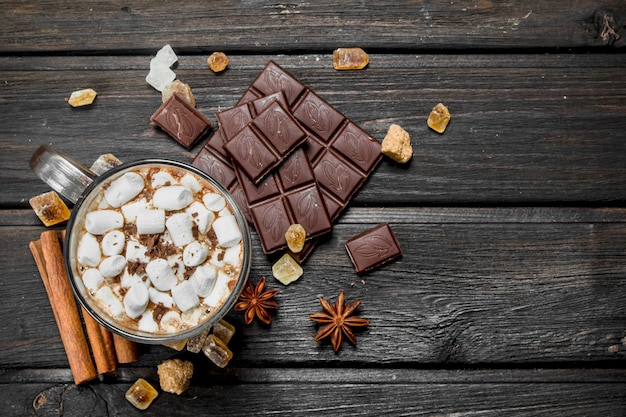 Hot chocolate with cinnamon and marshmallows. on a wooden table.
