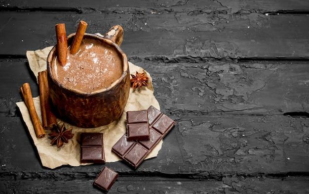 Hot chocolate with cinnamon sticks. on black rustic table.