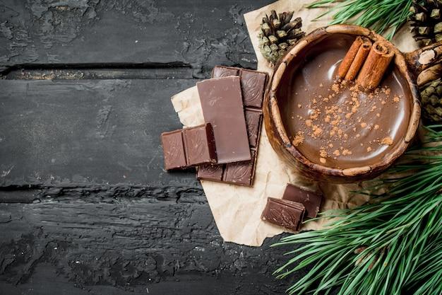 Hot chocolate with cinnamon sticks on black rustic table.