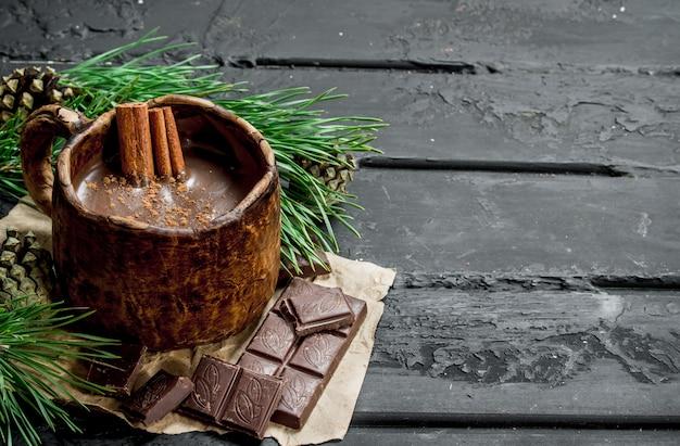 黒の素朴なテーブルにシナモンスティックとホットチョコレート。