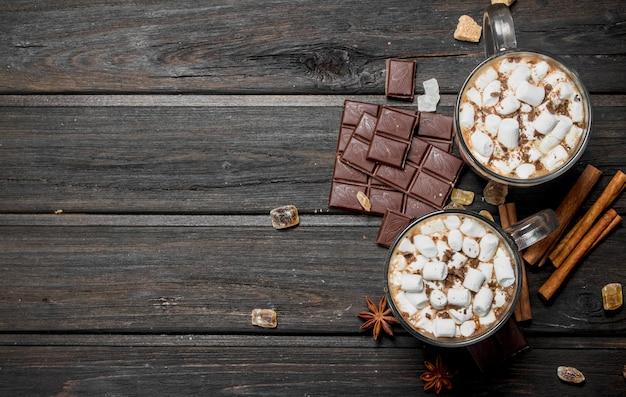 Горячий шоколад с зефиром корицы на деревенском столе.