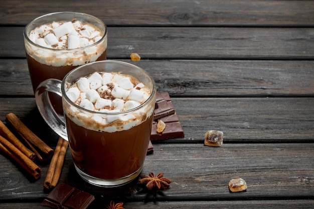Hot chocolate with cinnamonnd marshmallows on rustic table.