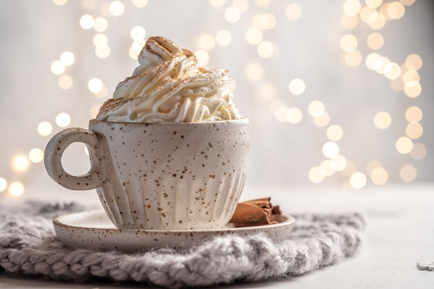Hot chocolate with cream and cinnamon stick in a ceramic cup.
