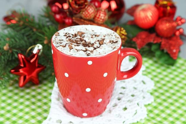 カラーマグカップ、ナプキン、クリスマスの装飾の背景にクリームとホットチョコレート