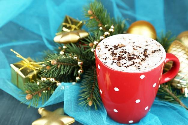 カラーマグカップ、テーブル、クリスマスの装飾の背景にクリームとホットチョコレート