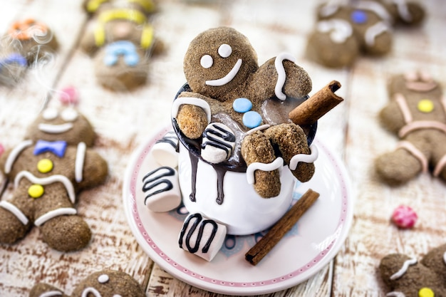 Hot chocolate with gingerbread man cookie and warm winter drink, fun food photo