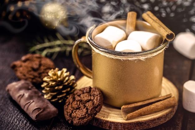 전형적인 크리스마스 및 휴일 음료인 금색 에나멜 머그에 제공되는 마시멜로 사탕과 핫 초콜릿