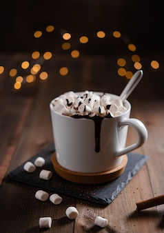 Hot chocolate with  marshmallow and cinnamon in a white mug on a wooden table