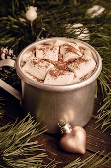 Hot chocolate with marshmallow and fir branches