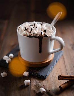 木製のテーブルの上の白いマグカップにマシュマロとホットチョコレート。マクロとクローズアップビュー。暗い写真