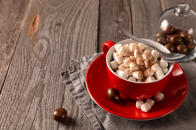 Hot chocolate with marshmallow in red cup on wooden table. christams winter hot drink menu recipe