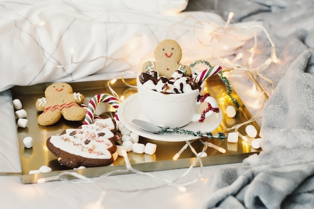 Hot chocolate with marshmallow, sweets and gingerbread man