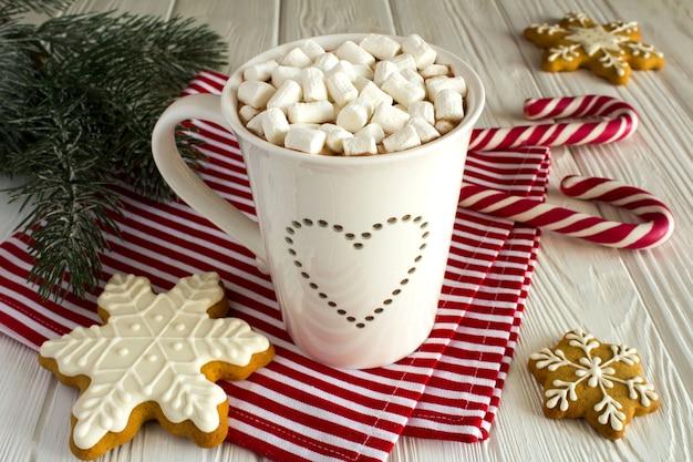 Горячий шоколад с зефиром и рождественской композицией на белом деревянном фоне