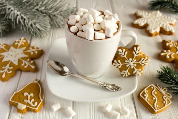 マシュマロと白い木製の表面にクリスマスクッキーとホットチョコレート