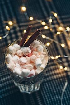 マシュマロとシナモンスティックのホットチョコレート。クリスマスと新年の背景。上面図