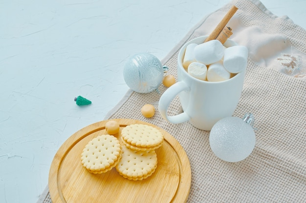 Hot chocolate with marshmallows and cinnamon cookies on tray tablecloth on white table the concept o...