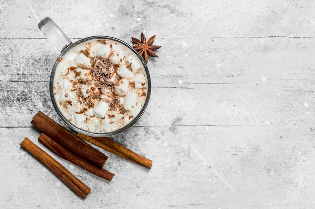 Hot chocolate with marshmallows and cinnamon on rustic table.