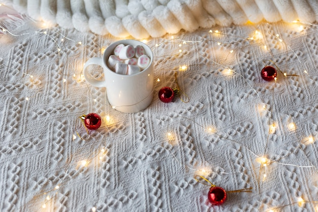 Hot chocolate with marshmallows, festive light garland and red christmas tree toys on a white bed.
