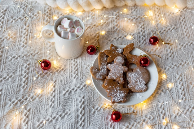 Hot chocolate with marshmallows and ginger cookies, festive light garland and red christmas tree toys on a white bed
