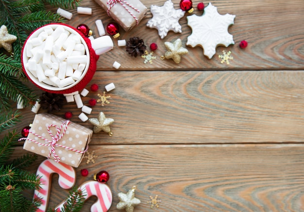 Hot chocolate with marshmallows and gingerbread cookies on a wooden background