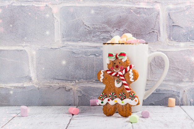 Hot chocolate with marshmallows and gingerbread girl cookie toy