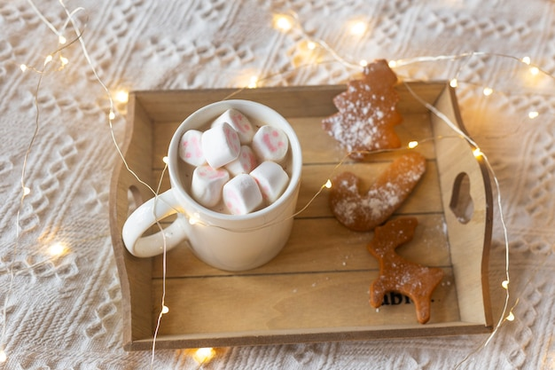 Hot chocolate with marshmallows and gingerbreads, festive light garland and red christmas tree toys on a white bed.
