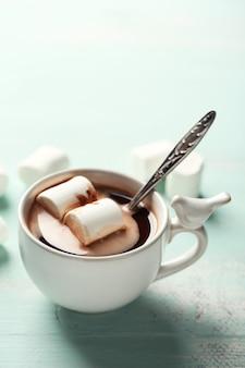 색상 나무 배경에 머그에 마시멜로와 핫 초콜릿