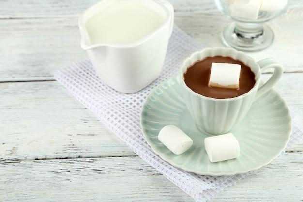 머그에 마시멜로를 넣은 핫 초콜릿, 컬러 나무 테이블, 밝은 배경