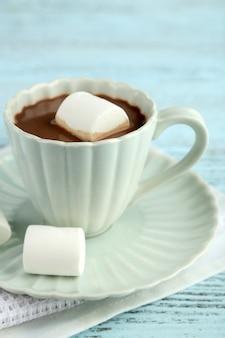 Горячий шоколад с зефиром в кружке, на цветном деревянном столе, на светлой поверхности