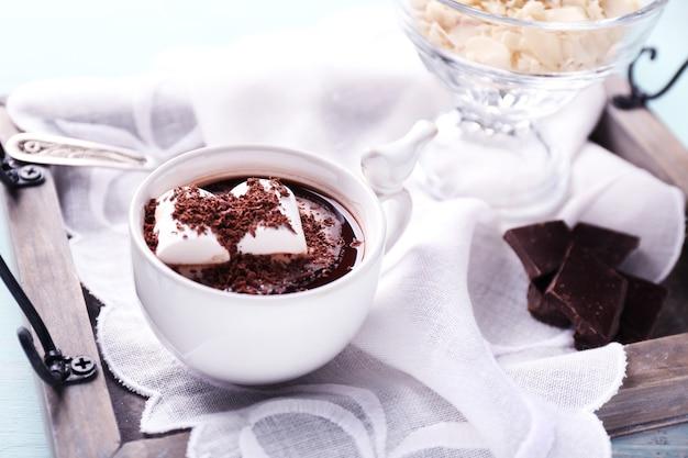 컬러 나무 배경의 트레이에 머그에 마시멜로를 넣은 핫 초콜릿