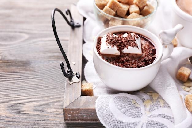 Горячий шоколад с зефиром в кружке, на подносе, на цветной деревянной поверхности