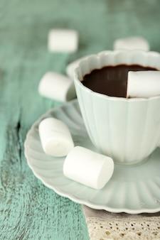 Горячий шоколад с зефиром в кружке на деревянном фоне