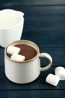 Горячий шоколад с зефиром в кружке на деревянной поверхности
