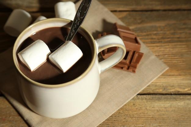 マグカップにマシュマロを入れたホットチョコレート、木の表面