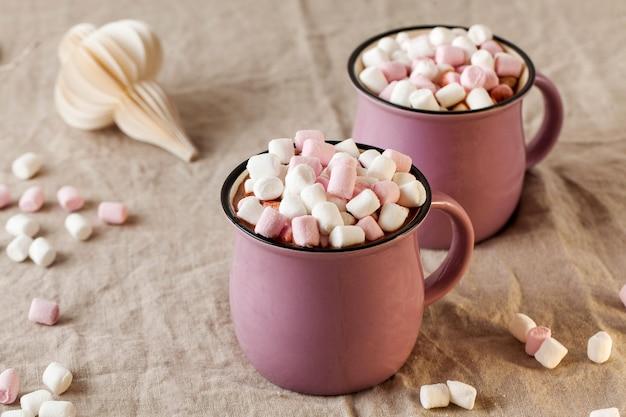 Горячий шоколад с маршмеллоу в кружках на льняной скатерти с елочной игрушкой