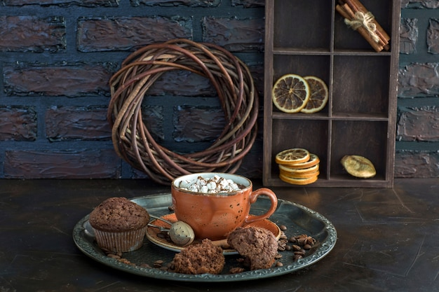 Hot chocolate with marshmallows and muffins on the table