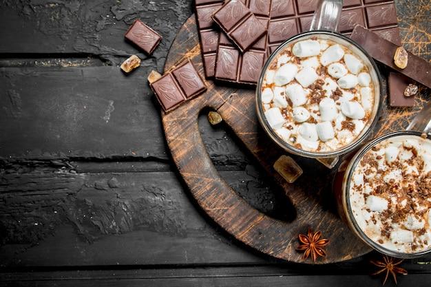 Горячий шоколад с зефиром на черном деревенском столе.