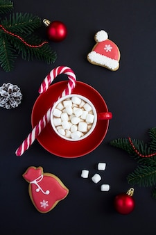 Hot chocolate with marshmallows in the red cup and christmas composition on the black  background. location vertical.