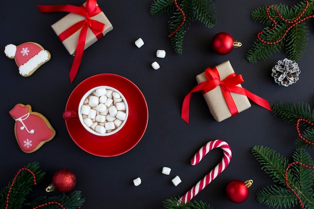 Hot chocolate with marshmallows in the red cup and christmas composition on the black  background. top view.