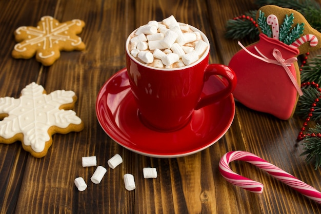 Hot chocolate with marshmallows in the red cup and christmas gingerbreads  on the brown wooden background