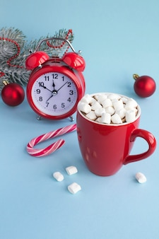 Hot chocolate with marshmallows in the red cup, red alarm clock and christmas composition