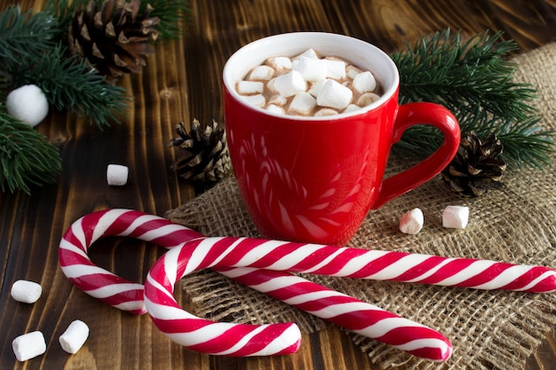 Hot chocolate with marshmallows in the red cup on the rustic  wooden background
