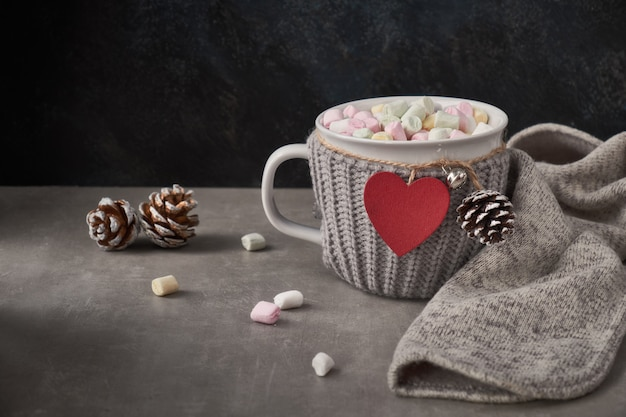 Hot chocolate with marshmallows, red heart on the cup on the table with winter decorations. birthday or valentine's day .