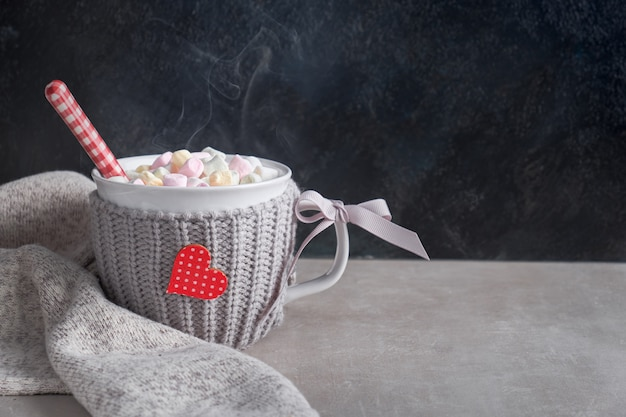 Hot chocolate with marshmallows, red heart on the cup on the table