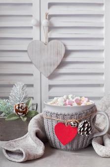 Горячий шоколад с зефиром, красное сердце на чашке на столе с зимними украшениями